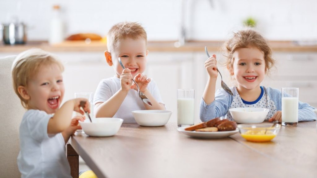 3 children eating on a table