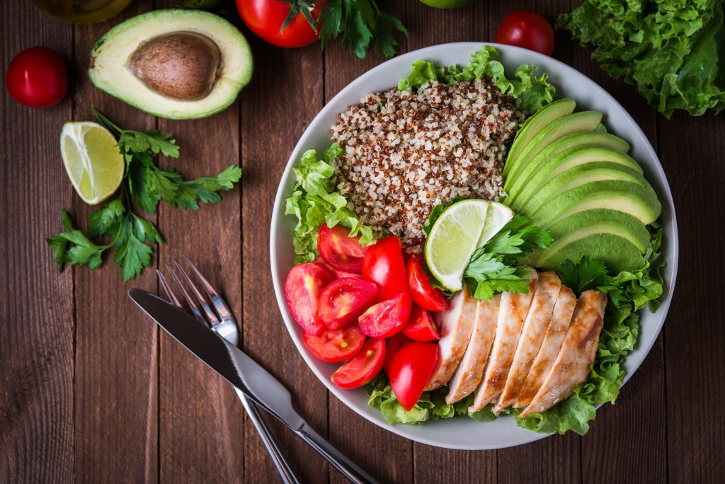 Healthy salad bowl with quinoa, tomatoes, chicken, avocado, lime and mixed greens (lettuce, parsley) on wooden background top view. Food and health.