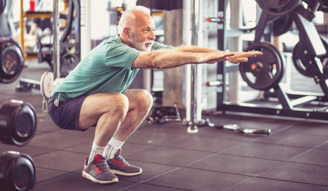 Old man squatting down at the gym